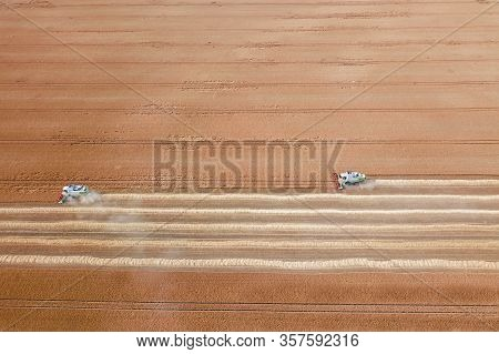 Combine Harvester Working On A Wheat Field. Combine Harvester Aerial View.