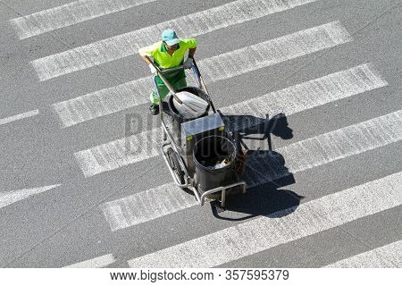 Street Sweeper Pushing A Cart On Crosswalk. Public Cleaning Concept