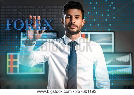 Bi-racial Trader Gesturing And Looking At Camera Near Forex Letters