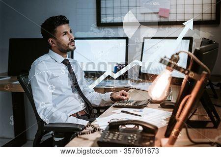 Pensive Bi-racial Trader Sitting Near Computers, Charts And Graphs