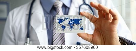 Close-up Of Doctor Hand Holding Plastic Credit Bank Card. Practitioner In Uniform With Stethoscope.