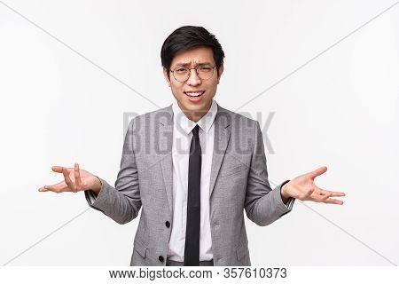 Why What Do You Want. Waist-up Portrait Of Bothered And Frustrated Young Asian Man In Grey Suit Bein