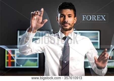 Selective Focus Of Bi-racial Trader Pointing With Fingers Near Computers And Forex Letters