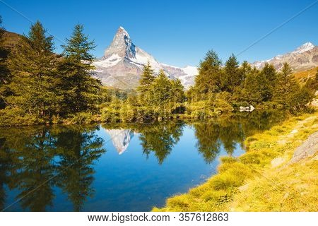 Scenic view of Matterhorn spire. Location Grindjisee lake, Cervino peak, Swiss alp, Switzerland, Europe. Image of popular tourist attraction. Exotic place in the world. Discover the beauty of earth.