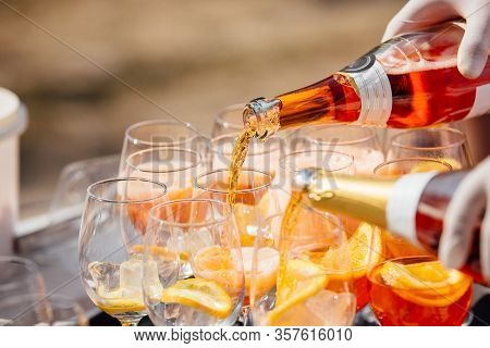 Barman Pours Sparkling Wine Into A Glass In Aperol Spritz Cocktail Outdoors Picnic