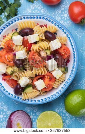 Bowl of cheese salad with fusili pasta and fresh vegetables