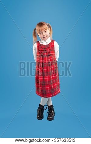 Cute Little Girl In Red Plaid Sundress And White Formal Shirt And Black Shoes Looking At Camera With