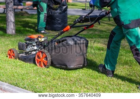 Man Moves With An Electrician To A Lawnmower And Mows Green Grass In The Backyard. Garden Cleaning S