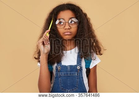 Clever African American Kid In Glasses Scratching Head With Pencil And Looking Away While Thinking O