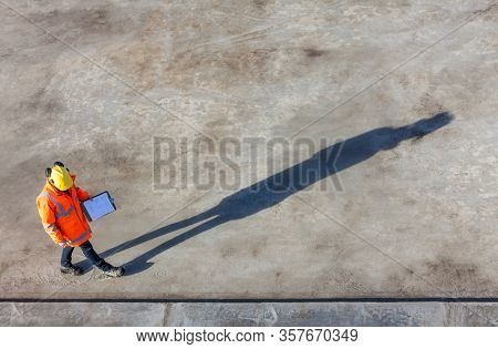 Overhead aerial view of anonymous construction worker or builder wearing a hi vis jacket, a hardhat and carrying a clipboard on a building site with their shadow stretching out in front of them