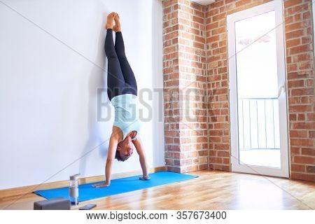 Middle age beautiful sportwoman smiling happy on mat. Practicing yoga doing wall-assisted handstand pose at gym