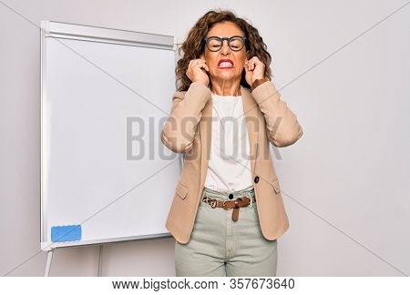 Middle age senior business woman standing on seminar presentation by magnectic blackboard covering ears with fingers with annoyed expression for the noise of loud music. Deaf concept.