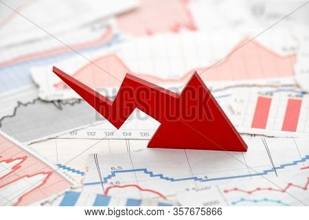 Financial crisis concept with falling red arrow on financial charts from newspapers