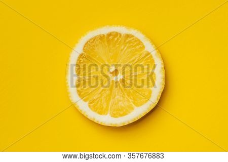 Slice of yellow lemon on yellow background. Top view.