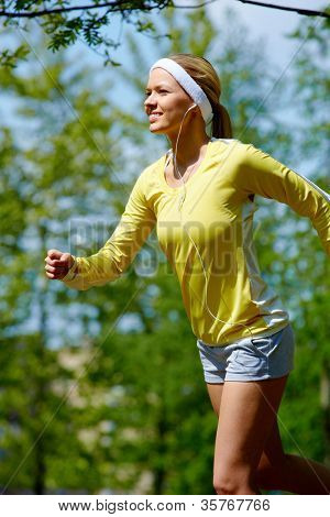 Portrait of a young woman jogging with a walkman