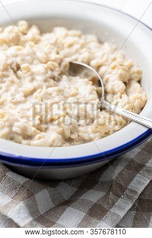 Bowl of oatmeal porridge on checkered napkin.