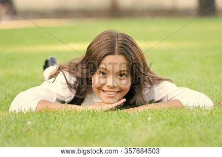 Keep Calm And Relax. Happy Child With School Look Lying On Green Grass. Little Girl Smile With Forma