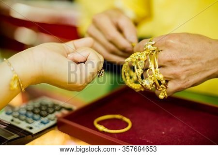 The Hands Of Women Customers And Salespeople Trying To Wear Bracelets Of Various Types Of Gold Jewel