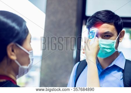 Selective Focus To Hand Of Staff Holding Digital Thermometer To Check Fever Visitor At Information C