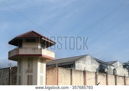 Prison Watchtower Protected By Wire Of Prison Fence.white Prison Wall And Guard Tower With Coiled Ba
