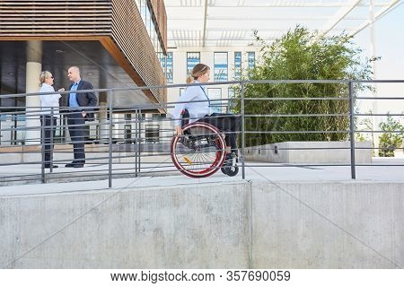 Woman in a wheelchair traveling on a ramp for accessibility and inclusion