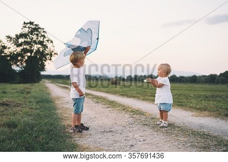 Children Playing With Kite On Nature In Countryside.