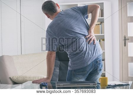 Man in home office suffering from low back pain sitting at a desk with notebook, papers and other objects