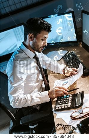 Bi-racial Trader Using Calculator And Holding Charts And Graphs Near Money Signs