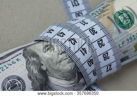 dollars with measuring tape closeup
