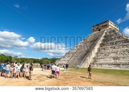 Chichen Itza, Mexico - Dec. 23, 2019: Tourists Visit The Famous Kukulcan Pyramid At Chichen Itza In
