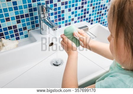Child washing hands with soap and water performing basic protective measures against spreading of coronavirus epidemy