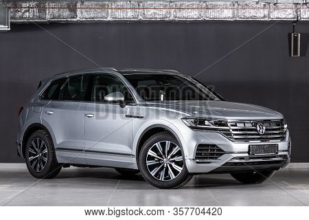 New Silver Volkswagen Touareg- Front View On Dark Background.   Modern Crossover Made In Germany . N
