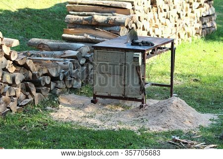 Vintage Old Metal Circular Saw Table With Rubber Gloves Next To Stacked Firewood Ready For Sawing Su