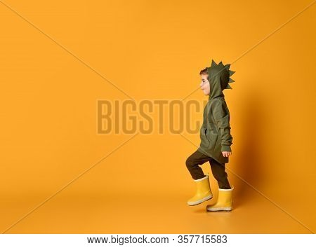 Surprised Kid Boy In Hoodie With Dinosaurus Spikes At His Back And Cowl And In Yellow Rubber Boots W