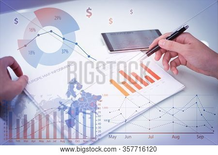 Businessman Examining Report With Financial Analysis Graphs. Caucasian Businessman Sitting At Table
