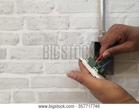 Electrician Installing Wall Socket For Electrical System Work On Gray Brick Wall.technician Installa