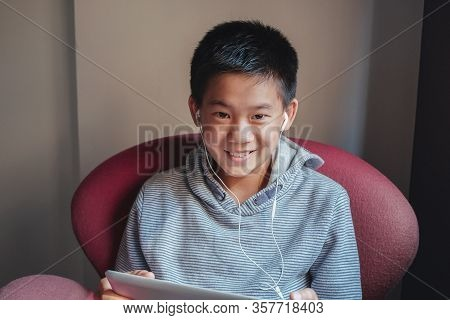 Oung  Mixed Asian Preteen Boy Using Digital Tablet At Home, Listening To Podcast, Gaming, Online Edu