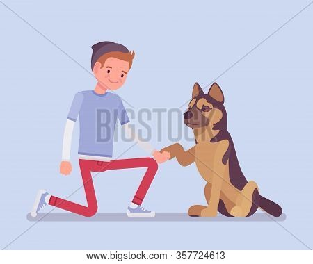 Boy With A Pet Dog Friend. Happy Guy Teaching Cute Puppy Giving A Paw Shaking Hand, Human And Animal