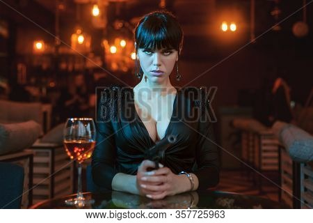 Sexy Young Woman Holding A Gun In Her Hands And Looking Angrily.