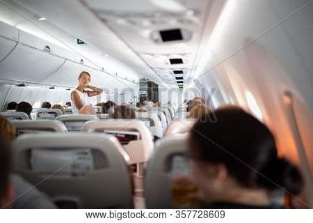 Pretty, young happy woman aboard an airplaneduring a lang haul commercial flight - stretching her legs and sore neck a bit, walking in the aisle
