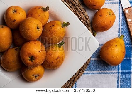 Fresh Loquats (medlars) On Blue Checkered Tablecloth Background Rustic And Healthy Appearance. Close