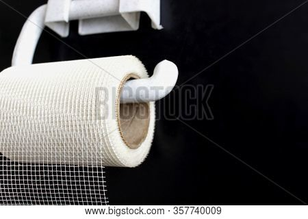 The Concept Of Inadequate Savings. Mesh Fiber Hangs On Toilet Paper Holder On Black Background. Irra