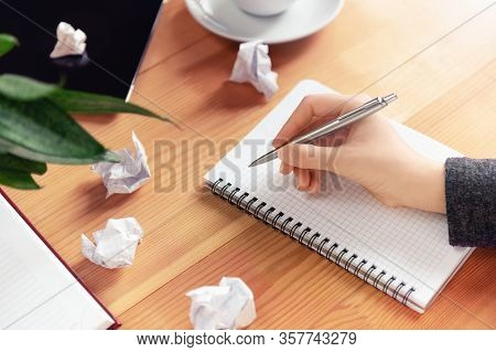 Workplace Of Writer, Rewriter. Female Hand Holding Pen And Writing In Notepad. Crumpled Paper And Cr