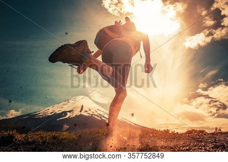 Woman trail runner runs with backpack on the gravel trail with snow capped volcano on the background and rocks flying in the air on the foreground