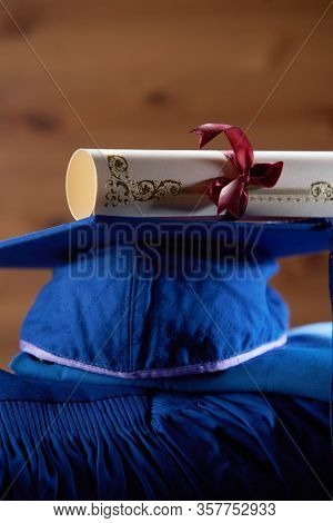 graduation grown  and mortar board on wooden background