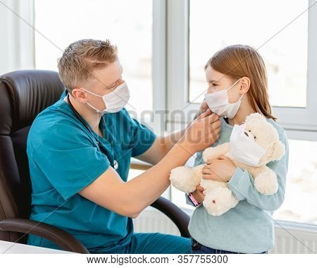 Kind doctor putting medical mask on little girl in clinic