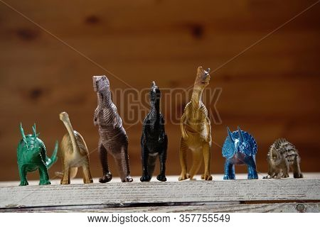front view group of the toy dinosaur with wooden background