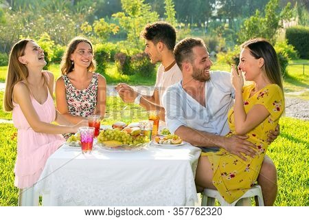 Group Of Friends And  Couple Enjoying Picnic Party In A Park On A Sunny Day.
