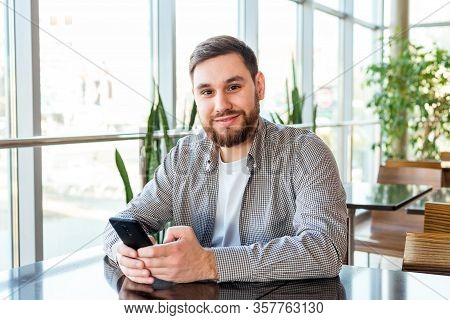 Smart Phone Texting. Attractive Bearded Caucasian Businessman Using Smartphone While Sitting In Offi