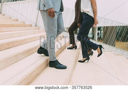 Businesspeople Moving Upstairs And Downstairs. Legs And Feet Of Business Man And Women Wearing Forma